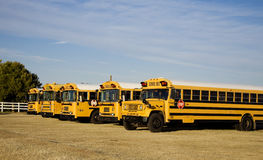 School buses parked outside school Stock Photos
