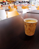 School cafeteria. A paper cup of coffee on the table of a university school lunch cafeteria, with new furnishings of bright orange and white. Wooden brown table Stock Photo