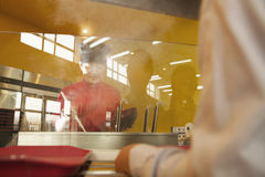 School cafeteria worker serves noodles to students Royalty Free Stock Images