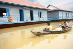 The School on Cambodia's lake and boys on boat Royalty Free Stock Photos