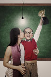 School champion holding trophy kiss by mum in class Royalty Free Stock Image