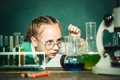 School chemistry lessons. Child in the class room with blackboard on background. School concept. Chemistry science
