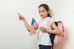 School child with a backpack holds the US flag, background bright wall in the school, Point with your finger location of copy spac. E Royalty Free Stock Photos