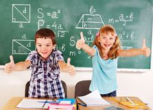 School child sitting in classroom. Group of school child sitting on desk in classroom stock images