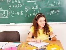 School child sitting in classroom. School child sitting on desk in classroom royalty free stock images