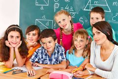School child sitting in classroom. Group of school child sitting on desk in classroom stock photography