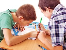 School child sitting in classroom. Group of school child sitting on desk in classroom stock image