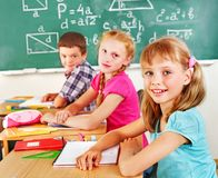 School child sitting in classroom. Group of school child sitting on desk in classroom royalty free stock photo
