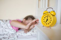 Yellow clock is on the table shows seven o`clock. school child wakes up and turns off the alarm. stock photography