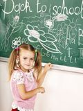 School child writing on black board. Royalty Free Stock Photo