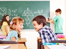 School child writting on blackboard. Royalty Free Stock Image