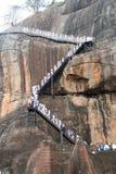 School children climbing Sigiriya Rock. Metal staircase to 'heaven' top of Sigiriya Rock - school children dressed in their white school uniform Stock Photos