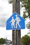 School children crossing sign. School children crossing the street sign posted on the wooden post Royalty Free Stock Image