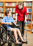 School Children with Disabilities. Two disabled kids in the school library, one in a wheelchair and one with crutches Royalty Free Stock Image