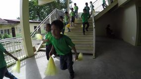 School children going down the stairs to perform pom poms calisthenics. Laguna, Philippines - September 3, 2015: Public elementary grade school pupils perform stock video footage