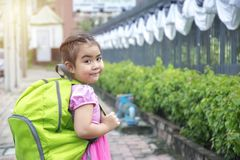 School children happily go to school. The girl Asia smiley face in a pink shirt with a green backpack,Education is important in laying the foundations of life Stock Photos