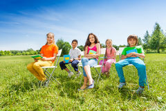 School children hold notebooks and sit on chairs Stock Photography