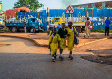 School children. Jinja, Uganda - September 2015 - School kids cross a downtown road with no zebra crossing. The children have to cross all roads in the town Royalty Free Stock Photo