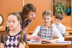 School children at lesson. Teacher monitoring.. Stock Photos