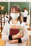School children in medical face mask. Are learning in the half empty classroom during epidemic of flu stock photos