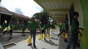 School children perform pom poms calisthenics. Laguna, Philippines - September 3, 2015: Public elementary grade school pupils perform dance exercise, a yearly stock video footage