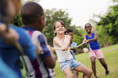 School children playing tug of war with rope. Children and recreation, group of happy multiethnic school kids playing tug-of-war with rope in city park. Summer Stock Images