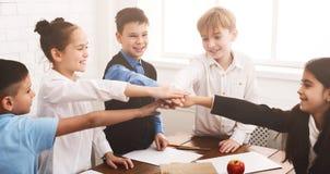 School children putting their hands together indoors. Unity concept. School children putting their hands together at school royalty free stock photo