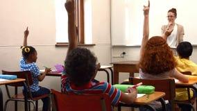 School children raising hands in class stock video