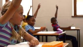 School children raising hands in class stock footage