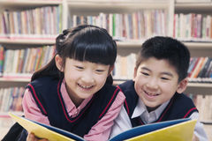 School children reading book a in the library Royalty Free Stock Images