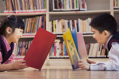 School children reading books in the library Stock Photo
