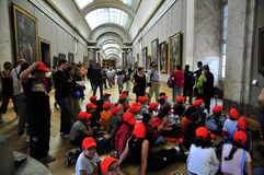 School children with red beanies  at the Louvre. Teacher and children at the Louvre Stock Images