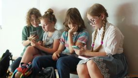 School children sit on a bench at school with their smartphones. Internet addiction, kids and gadgets, back to school