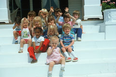 School children sitting on front porch Royalty Free Stock Images