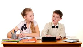 School children sitting by the table, doing stock video