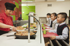 School children standing in line in school cafeteria royalty free stock photos