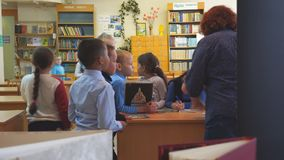 School children are standing next to the teacher`s desk. Chapaevsk, Samara region, Russia - May 10, 2019: Elementary school of the city of Chapaevsk. Woman stock video