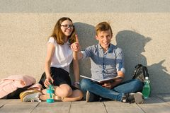 School children teens sit on gray wall, read textbooks, drink water, look at textbook. Boy looking at book and pointing forefinger royalty free stock image