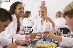 School children and their teacher in science class Royalty Free Stock Images