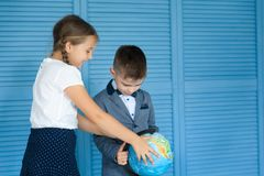 School children. Back to school. School children in a uniforn looking at the globe. Back to school Royalty Free Stock Photo