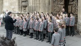 School choir singing Christmas carols in front of Bath Abbey A. Bath, England - Nov 27, 2017: School choir singing Christmas carols in front of Bath Abbey A royalty free stock photography