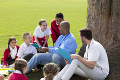 School Class Outdoors. Small group of children sitting on the grass having a lesson outdoors. Two male teachers can be seen. The children look to be listening Stock Photography