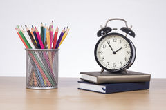 School classes and education concept. With a collection of brightly colored pencil crayons in a basket alongside an alarm clock and books on a wooden table Royalty Free Stock Photo