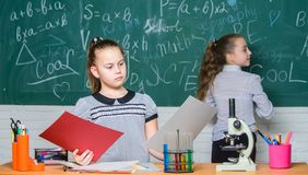 School classes. Girls study chemistry in school. Microscope test tubes chemical reactions. Pupils at chalkboard. Fascinating science. Educational experiment royalty free stock images