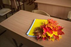 School classroom. notebook and bouquet of autumn maple leaves on the table. concept: back to school, teacher`s day. School classroom in blur background without stock photography