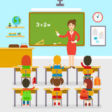 School classroom with teacher and pupils, education, elementary school, learning and people concept. Teacher woman by blackboard teaching students in classroom Stock Photography