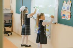 School. Classroom. Two little girls with white ribbons and dressed in school clothes, write on the interactive whiteboard stock images