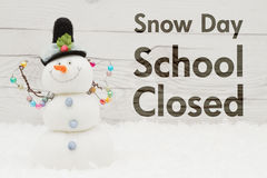 School Closed message with a snowman. School canceled message, A snowman with text Snow Day School Closed on weathered wood Stock Photo
