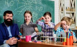 After school clubs. School chemistry experiment. Explaining chemistry to kid. Fascinating chemical reaction. Teacher and. Pupils test tubes in classroom stock photo