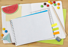 School collage. Writing-materials of the school student. A notebook in a ruler, a notebook on rings, a pencil, an eraser, a ruler, note paper, candies and the Stock Photo